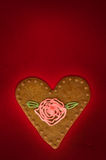 Valentines day greetings card. With heart shaped cookie on maroon background Royalty Free Stock Photography