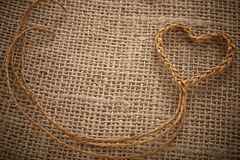 Valentines Day. Handmade Heart made of twine on sackcloth Stock Images
