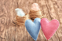 Love, Valentines Day. Hearts couple, wood. Vintage. Love, Valentines Day. Hearts couple Handmade and nests with feathers on wooden background. Vintage retro Stock Photos