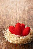 Love, Valentines Day. Hearts on wood. Couple nest. Love hearts, Valentines Day. Hearts handmade on wooden background. Couple made of red felt in straw nest Stock Images