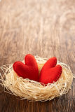Love, Valentines Day. Hearts on wood. Couple nest. Love hearts, Valentines Day. Hearts handmade on wooden background. Couple made of red felt in straw nest Royalty Free Stock Images