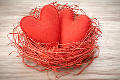 Love, Valentines Day. Hearts on wood. Couple nest. Love hearts handmade on wooden background. Valentines  Day. Couple made of red felt in straw nest. Vintage Stock Photography