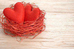 Valentines Day. Handmade Hearts Couple in Red nest. Love concept. Valentines Day. Handmade Red Hearts Couple in nest made of straw. Love concept on wooden Stock Images