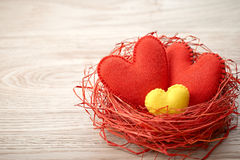 Valentines Day. Handmade Hearts Couple in Red nest. Love concept. Valentines Day. Handmade Red Hearts Couple in nest made of straw. Love concept on wooden Stock Photography