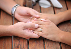 Valentines day hands. A married couple holding their hands on a table - valentines day Stock Photography