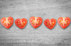 Valentines day. Healthy food with monochrome table wood style. Heart tomato shaped cut in half Royalty Free Stock Photos