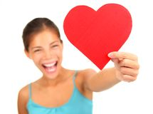 Valentines day heart. Woman holding Valentines Day heart sign with copyspace. Beautiful mixed race asian / caucasian model isolated on white background. Shallow Stock Images