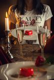 Valentines day, heart cake on white plate, romantic evening and gift, pretty woman with rose in hand. royalty free stock photo