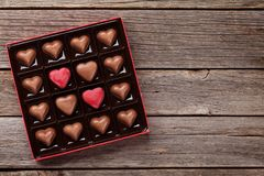 Heart shaped chocolate in box. Valentines day with heart chocolate in box on wooden table. Top view with space for your greetings Royalty Free Stock Image