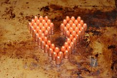 Valentines day heart made out of 9mm bullets. Bullets are on a rustic metal background Stock Images