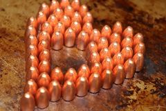 Valentines day heart made out of 9mm bullets. Bullets are on a rustic metal background Stock Image