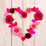 Valentines Day heart outline of paper roses and hearts over white wood. Valentines Day heart outline made of paper roses and hearts over a rustic white wood royalty free stock image