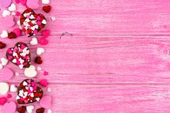 Valentines Day heart shaped candy side border against pink wood Stock Images