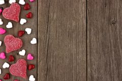 Valentines Day heart shaped candy side border on rustic wood Royalty Free Stock Photography