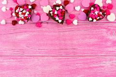 Valentines Day heart-shaped candy top border against pink wood Stock Photo