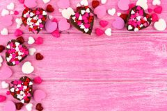 Valentines Day heart-shaped candy top corner border over pink wood Royalty Free Stock Image