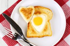 Valentines Day heart shaped egg and toast breakfast. Heart shaped egg in toast for Valentines Day on white plate with red and white checked cloth Royalty Free Stock Images