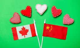 Valentines Day heart shapes and flags of Canda and China. On green background Royalty Free Stock Photos