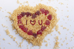 Valentines Day Heart with sign I love u. Valentines Day Heart with words I love you made from yellow biscuits crumbs and red candies on the white background Stock Photos