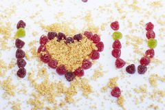 Valentines Day Heart with words I love u. Words I love u with Valentines Day Heart made from yellow biscuits crumbs and red candies on the white background Royalty Free Stock Image