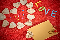 Valentines Day. Word Love, hearts and note on red. Love, Valentines Day. Word Love, hearts and note on red. Romantic style. Vivid unusual creative greeting card Stock Photography