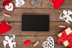Valentines day hearts, ring, gift box and the tablet over wooden background. Royalty Free Stock Images