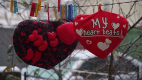 Valentines day. hearts soft pads hanging on a rope. In the yard stock video footage