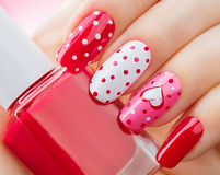 Valentines Day holiday manicure with painted hearts and polka dots. Valentines Day holiday style bright manicure with painted hearts and polka dots royalty free stock images