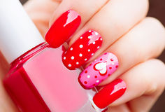 Valentines Day holiday manicure with painted hearts and polka dots Royalty Free Stock Photos
