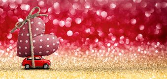 Valentines Day Incoming - Miniature Red Car. Carrying Heart and Glitter Background Royalty Free Stock Image