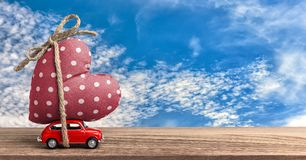 Valentines Day Incoming - Miniature Red Car Carrying Heart. And Sky Background Royalty Free Stock Photos
