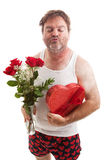 Valentines Day Kiss. Scruffy middle aged man in his underwear with flowers and candy for Valentines Day, puckering up for a kiss. Isolated on white stock image