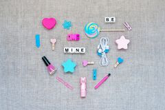 Valentines Day knolling heart made from a variety of pink and blue accessories, cosmetics and stationery and text BE MINE on linen. Fabric background. Valentine royalty free stock photos