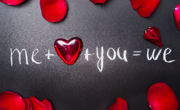 Valentines day lettering background with red hearts and rose petals, top view. Me plus you equals we. Stock Photo