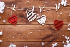 Valentines day love background, red white decorative hearts hanging on brown wooden table with snow falling, happy romantic. Holiday card on February 14, dating royalty free stock images