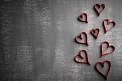 Valentines day and love concept. Many paper red hearts on gray wooden background stock images