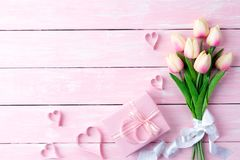 Valentines day and love concept. Pink paper hearts with gift box. And tulips with ribbon on pink pastel wooden background stock image