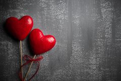 Valentines day and love concept. Two handmade red hearts with red ribbon on gray wooden background stock photography