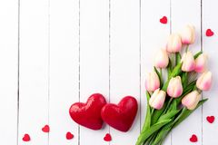 Valentines day and love concept. Two handmade red hearts with tulips. On white wooden board royalty free stock photography