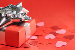 Valentines Day love gift. Valentines Day gift in box and small hearts on red background Stock Photo