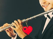 Male flutist with flute and heart. Love melody Stock Image
