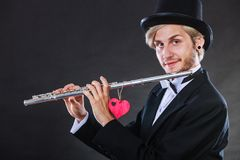 Male flutist with flute and heart. Love melody Stock Photography