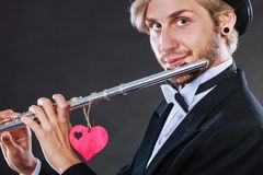 Male flutist with flute and heart. Love melody. Valentines day love melody concept. Flute music playing male flutist musician performer. Young elegant stylish Stock Photo