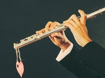 Male flutist with flute and heart. Love melody Royalty Free Stock Photography