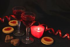 Two crystal glasses of wine, candles and sweets. Red is the color of passion. Romantic date. Be my Valentine royalty free stock image