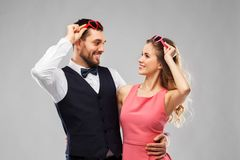 Happy couple in heart-shaped sunglasses royalty free stock images