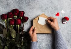 Valentines day man hand holding envelope love letter with greeting card. Mothers day red rose gift surprise on grey background with copyspace. Love flower gift stock photography