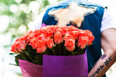 Valentines day. Man hiding behind a bouquet of flowers. Royalty Free Stock Photos