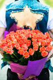 Valentines day. Man hiding behind a bouquet of flowers. Stock Photo