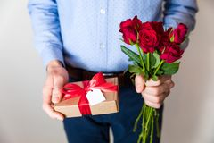 Valentines day,man holding red roses and gift with bow and tag,romantic surprise stock photo